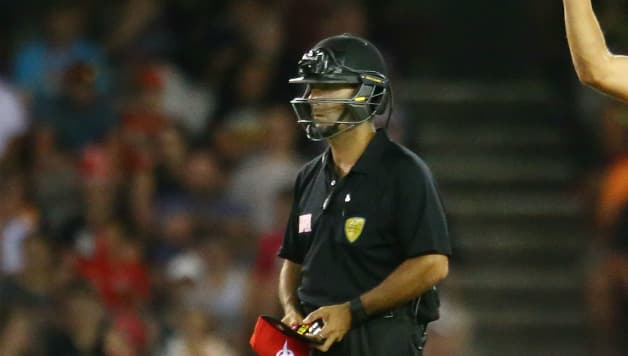 Umpire Gerard Abood pictured in a batting helmet during the BBL clash © Getty Images