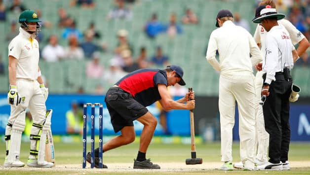 Steve Smith of Australia and bowler Stuart Broad of England look on as the groundsman tries to flatten the bowlers foot marks on the pitch   © Getty Images