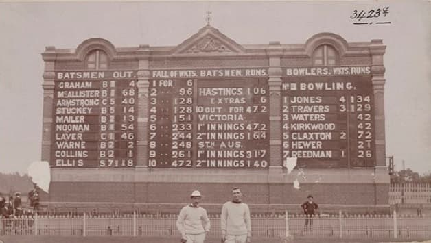 Thomas Hastings (left) and Matthew Ellis (right) in front of the Melbourne Cricket Ground scoreboard that displays their scores. Photographer: John Beaumont (the picture is now out of copyright)