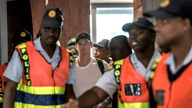 Steven Smith escorted by security at the Johannesburg airport © AFP