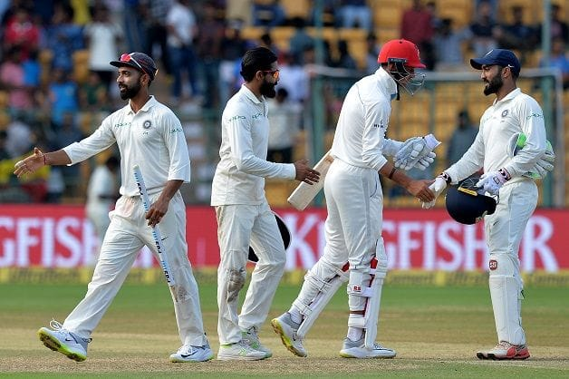 It's all over. The players shake hands as India send Afghanistan packing inside two days at Bengaluru, in 2018 © AFP