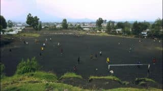 An India-Pakistan cricket match on Congolese volcanic rocks amidst goats