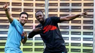 Usain Bolt participates in a cricket match against Yuvraj Singh